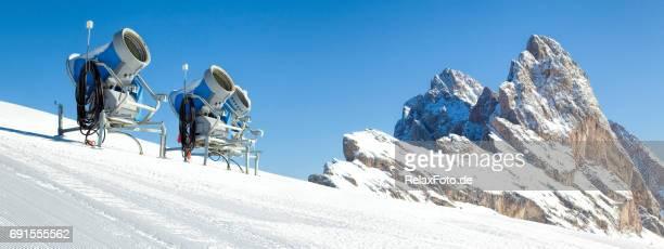 Trois souffleuses à neige sur la piste de ski avec formation rocheuse aux sommets enneigés dans Dolomites, Haut-Adige, Italie