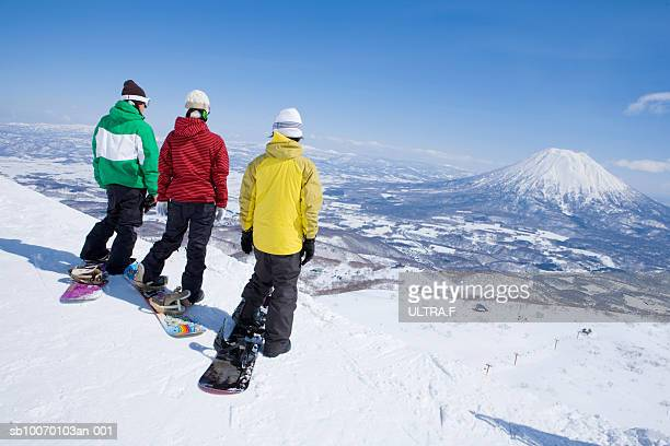 Three snowboarders on edge of slope, rear view