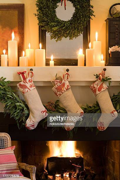 three socks stuck on christmas fireplace - christmas stocking stock photos and pictures