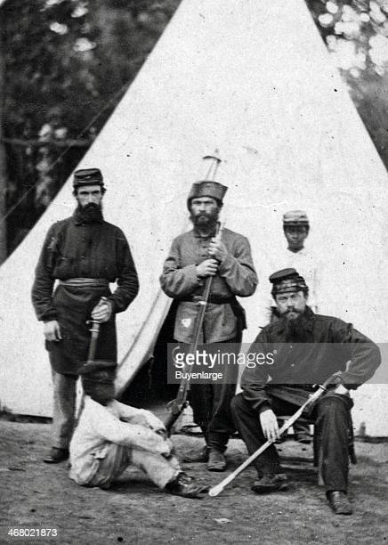 Three soldiers and two AfricanAmerican children probably servants posing in front of a tent 1863
