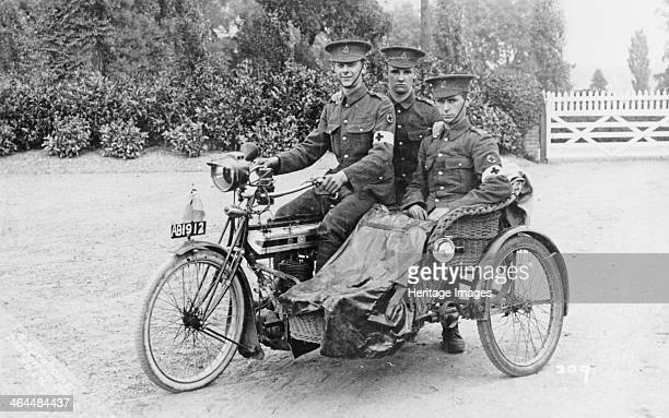 Three soldiers on a bicycle and sidecar They are wearing Red Cross armbands indicating that they are medics