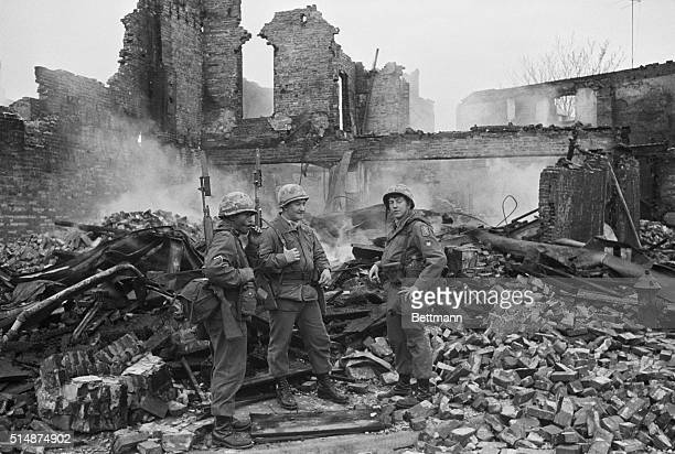 Three soldiers stand amid the rubble of a burned building in Washington DC Riots and looting occurred in many US cities after the assassination of Dr...