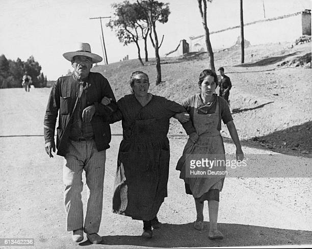 Three Spanish refugees help one another on their journey across the border to France to escape the fascist forces who have taken over their homes in...
