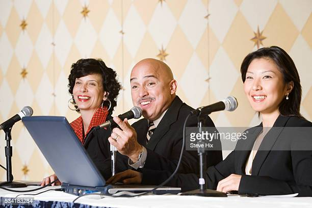 Three speakers at a conference