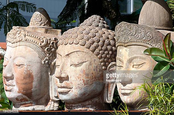 three stone buddha heads sit beside each other amongst trees - bodhisattva stock pictures, royalty-free photos & images