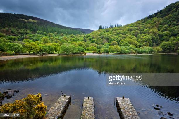 Three stone docks along Upper Lake in Wicklow Mountains National Park by Glendalough, stormy spring skies