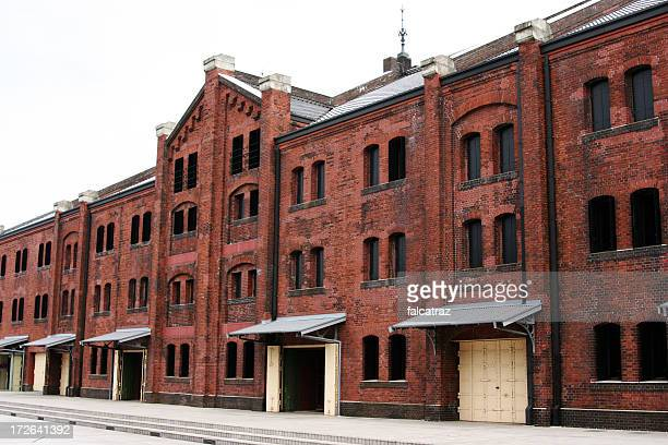 Three story old red brick warehouse with black windows