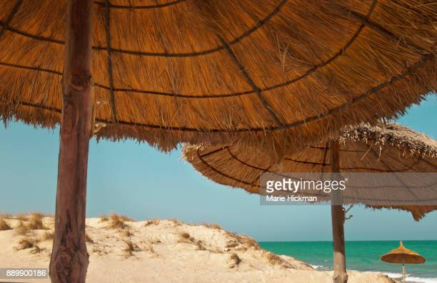Three straw umbrellas on Djerba Island Tunisia.