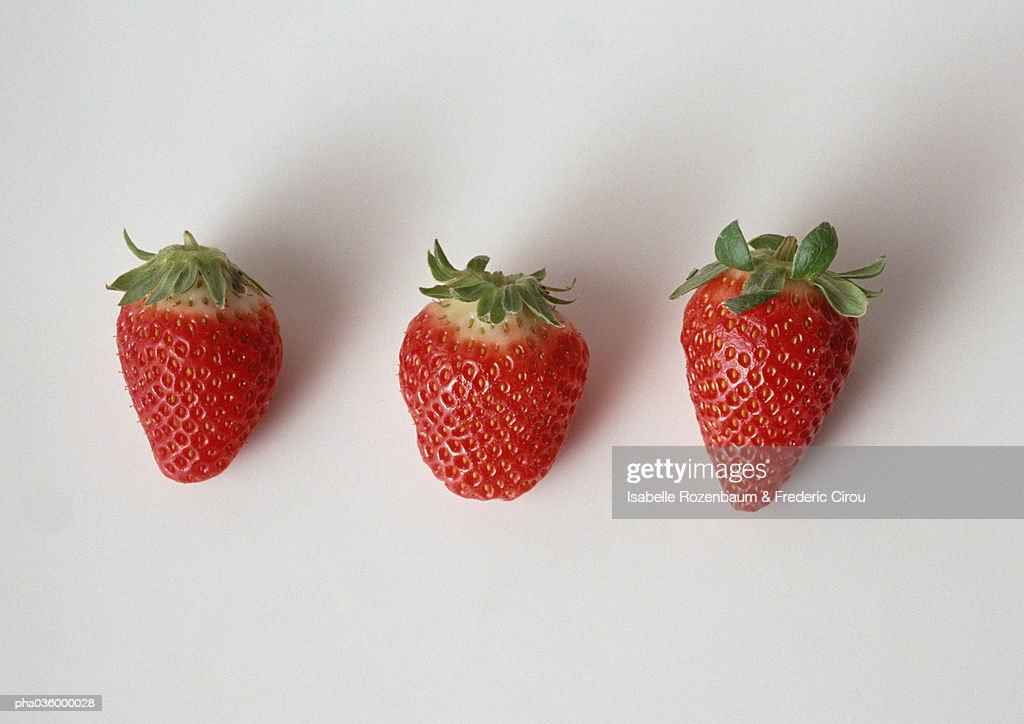 Three strawberries in a row, close-up, white background : 圖庫照片