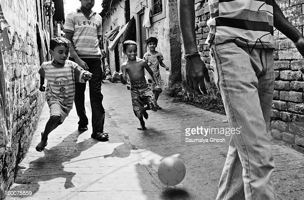 Three street children are playing football on the narrow lanes of north Calcutta. They are happily enjoying the game.
