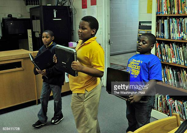 Three students Jarquiese McCaskey Jaquan Hawkins and Zaylan Randolph hold computers as they enter the school library where they will attempt to do...