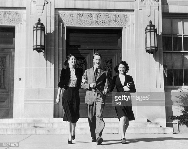Three students leave college arm in arm circa 1940