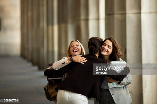 three students meet and hug outside the university. - universidad stock pictures, royalty-free photos & images