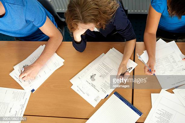 'Three students sitting at desk with worksheets, overhead view'