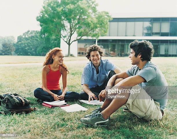 Three Students Sitting Outdoors on Campus