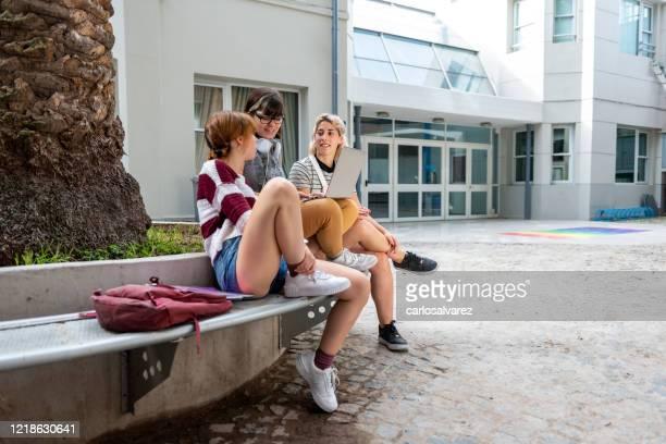 três estudantes conversando durante um intervalo - patio de colegio - fotografias e filmes do acervo
