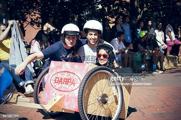 Three students wearing helmets pose for a photo from inside a wooden cart with wheels, as onlookers watch from the side in the shade, during a...