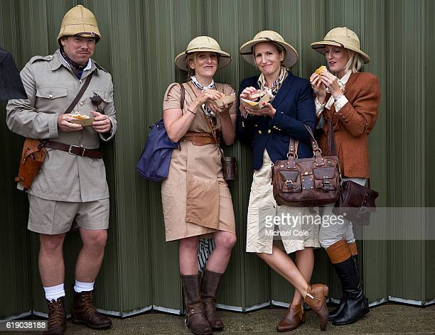 Three stylish ladies and a gentleman eating burgers and wearing Safari outfits and Safari Pith helmets at Goodwood on September 10 2016 in Chichester...