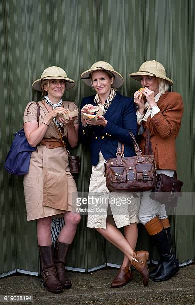 Three stylish ladies eating burgers wearing Safari outfits and Safari Pith helmets at Goodwood on September 10 2016 in Chichester England
