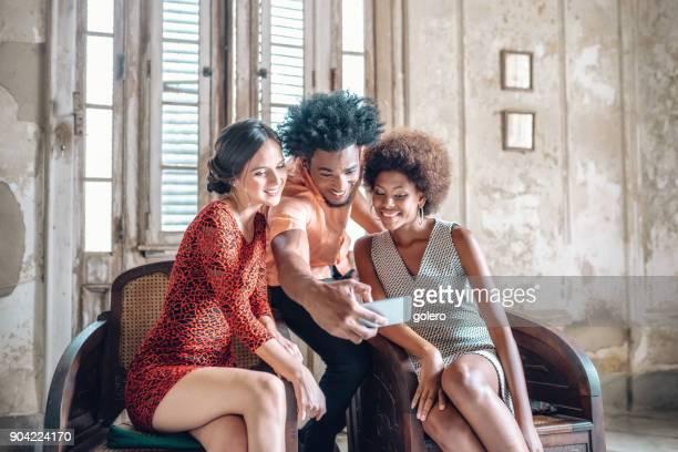 drei stilvolle junge kubanische Freunde Blick auf Mobile im Innenbereich