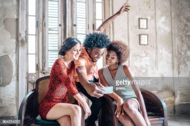 drei stilvolle junge kubanische Freunde nehmen Selfie auf Mobile indoor