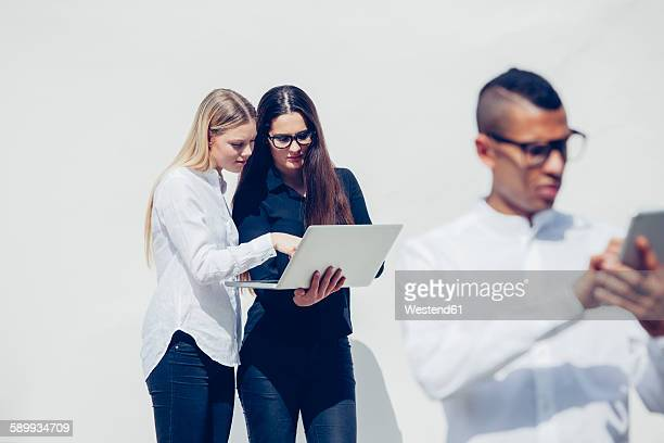 Three stylish young people with mini tablet and laptop in front of white background