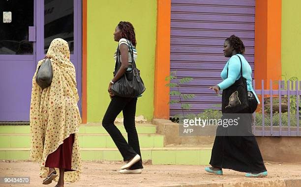 Three Sudanese women one of them wearing closefitting trousers walk on a main street in central Khartoum on September 8 as a Sudanese female...