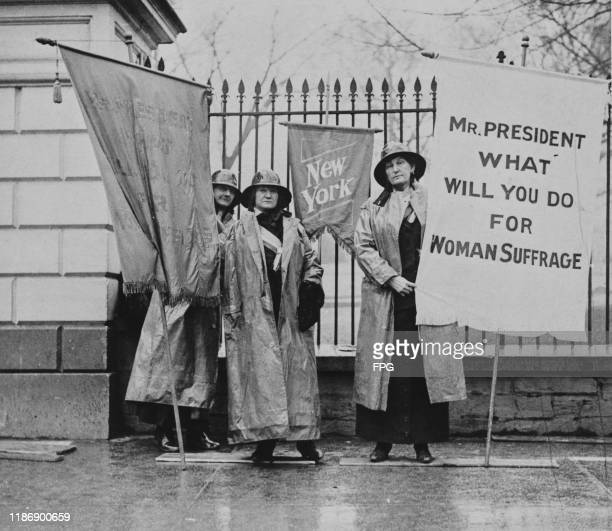 Three suffragists silent sentinels picketing outside the White House holding banner that reads 'Mr President What Will You Do For Woman Suffrage',...