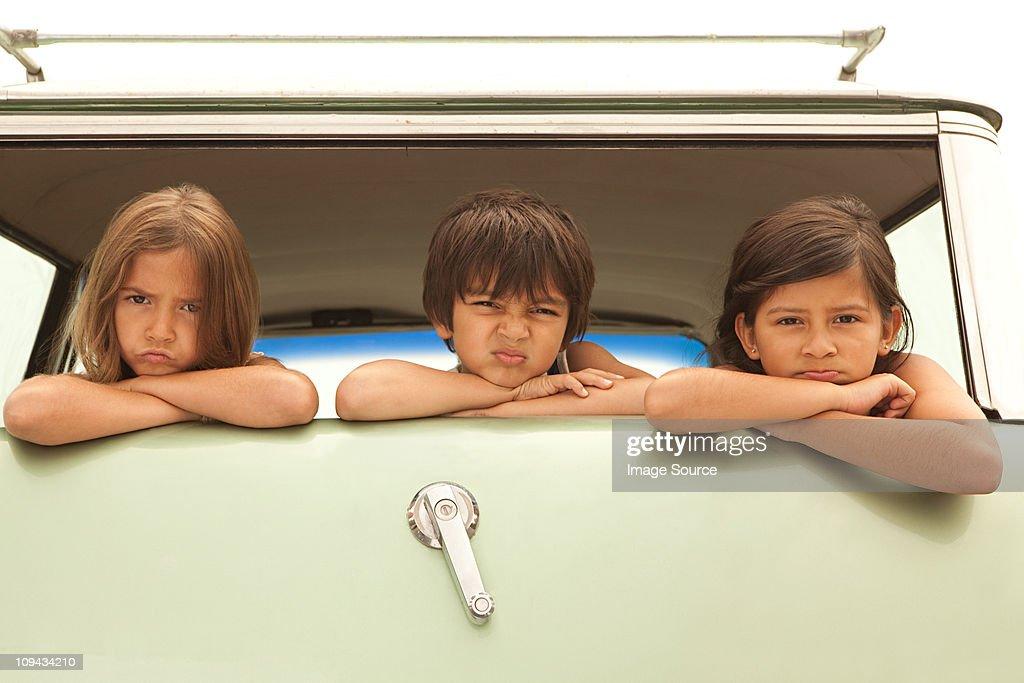Three sullen children in back of estate car : Stock Photo
