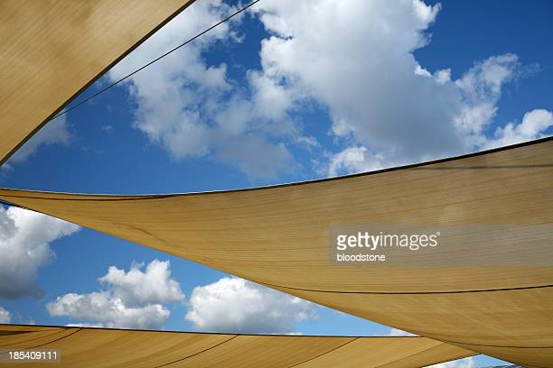 Three sun shade sails against a blue sky