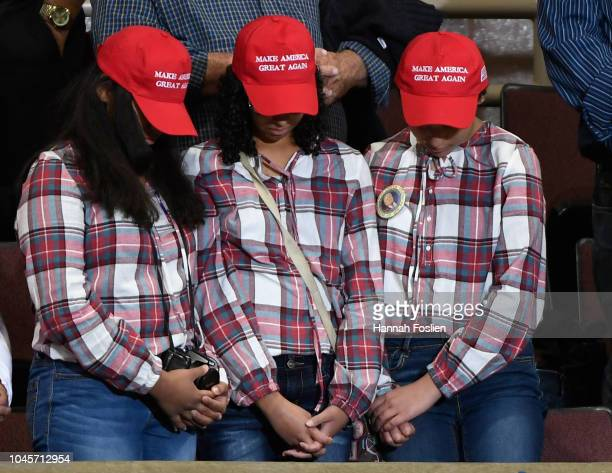 Three supporters bow their heads as a prayer is said at a campaign rally held by US President Donald Trump on October 4 2018 at Mayo Civic Center in...