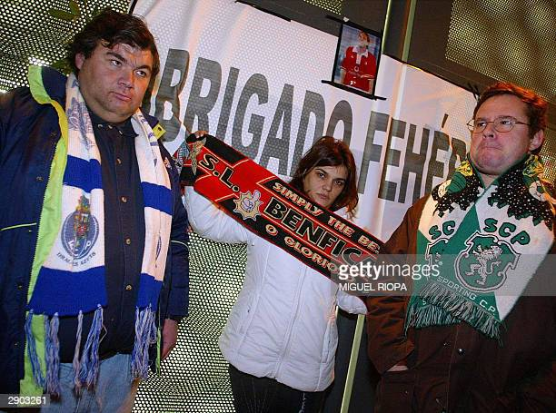 Three supporters of the Porto Benfica and Sporting Lisboa pose in the Luz Stadium at Lisbon 26 January 2004 near a placard that reads Obrigado Feher...