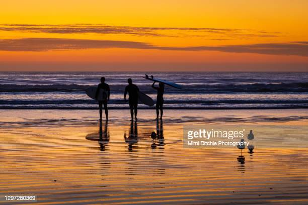 three surfers at sunset - pismo beach stock pictures, royalty-free photos & images