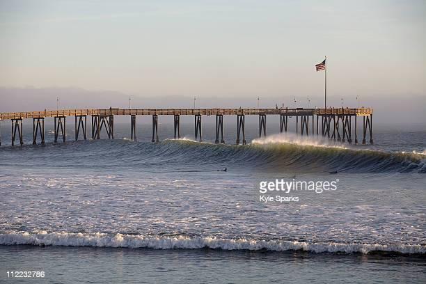 three surfers prepare to duck dive a large wave while surfing california street in ventura, california. - ベンチュラ市 ストックフォトと画像