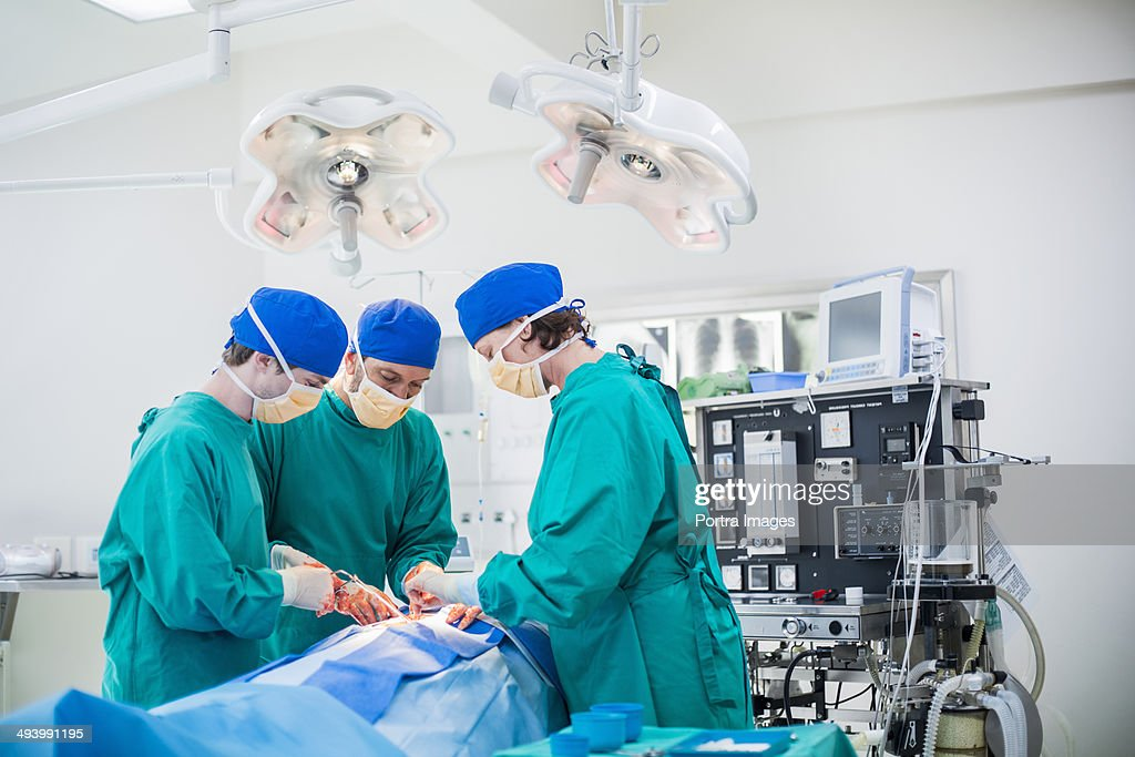 Three surgeons performing a surgery : Stock Photo