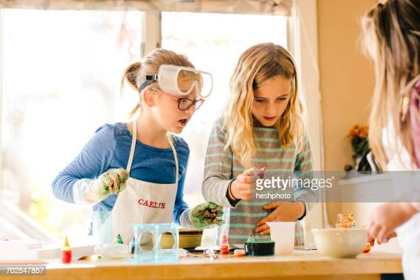three surprised girls doing science experiment, staring - heshphoto stockfoto's en -beelden