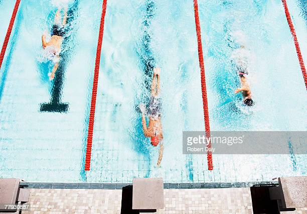 three swimmers coming to ledge of pool - sports race stock pictures, royalty-free photos & images
