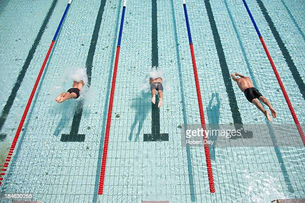 Three swimmers diving in pool