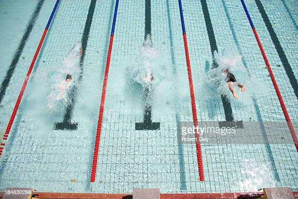 three swimmers diving in pool - length stock pictures, royalty-free photos & images