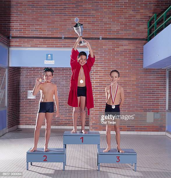 three swimmers on podium - winners podium stock pictures, royalty-free photos & images