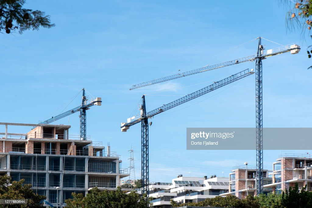 Three tall cranes and buildings under construction : Foto de stock