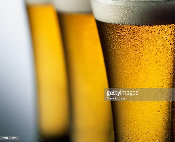 three tall glasses of beer - ラガービール ストックフォトと画像