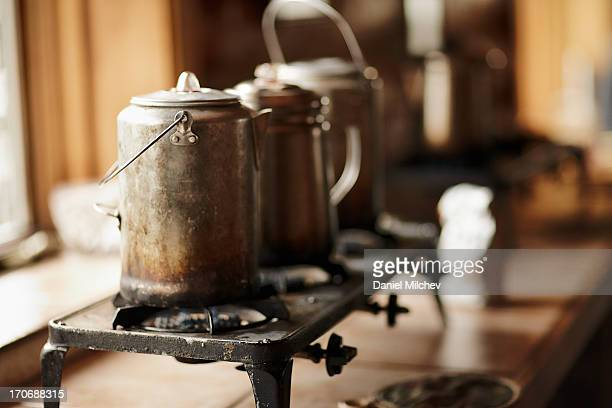 Three teapots on a gas burner in an old hut.