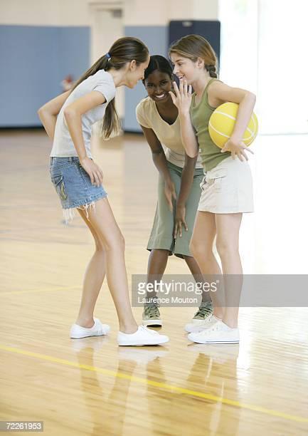 three teen girls huddling in school gym - girls with short skirts - fotografias e filmes do acervo
