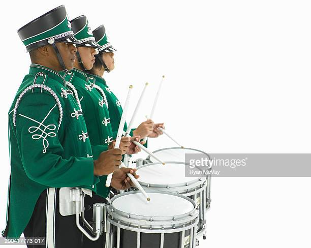 Three teenage boys (14-17) in band uniforms carrying drums, side view