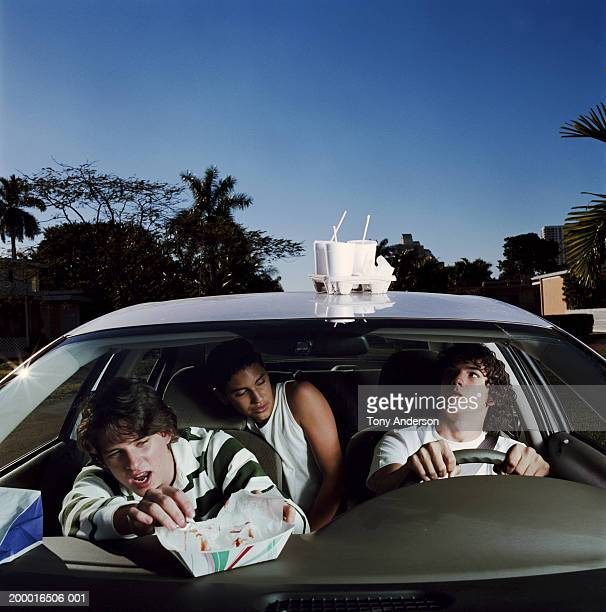 three teenage boys (15-17) in car with beverages on rooftop - inconvenience stock pictures, royalty-free photos & images