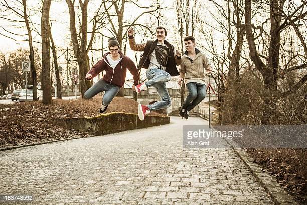 three teenage boys jumping in park - só meninos adolescentes imagens e fotografias de stock
