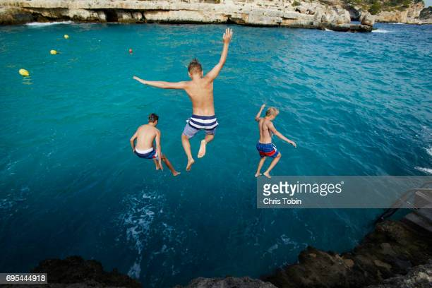 three teenage boys jumping into blue water with arms outstretched - coraggio foto e immagini stock