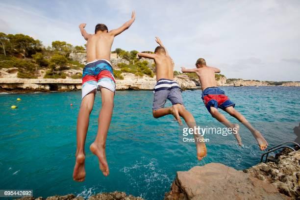 three teenage boys jumping off cliff into blue water - jungen in badehose 12 jahre stock-fotos und bilder