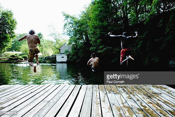 Three teenage boys (14-19) jumping off jetty